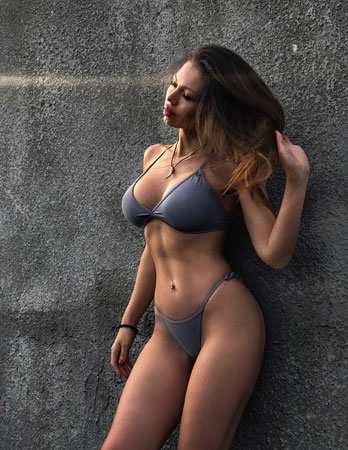 woman standing against a wall wearing only underwear